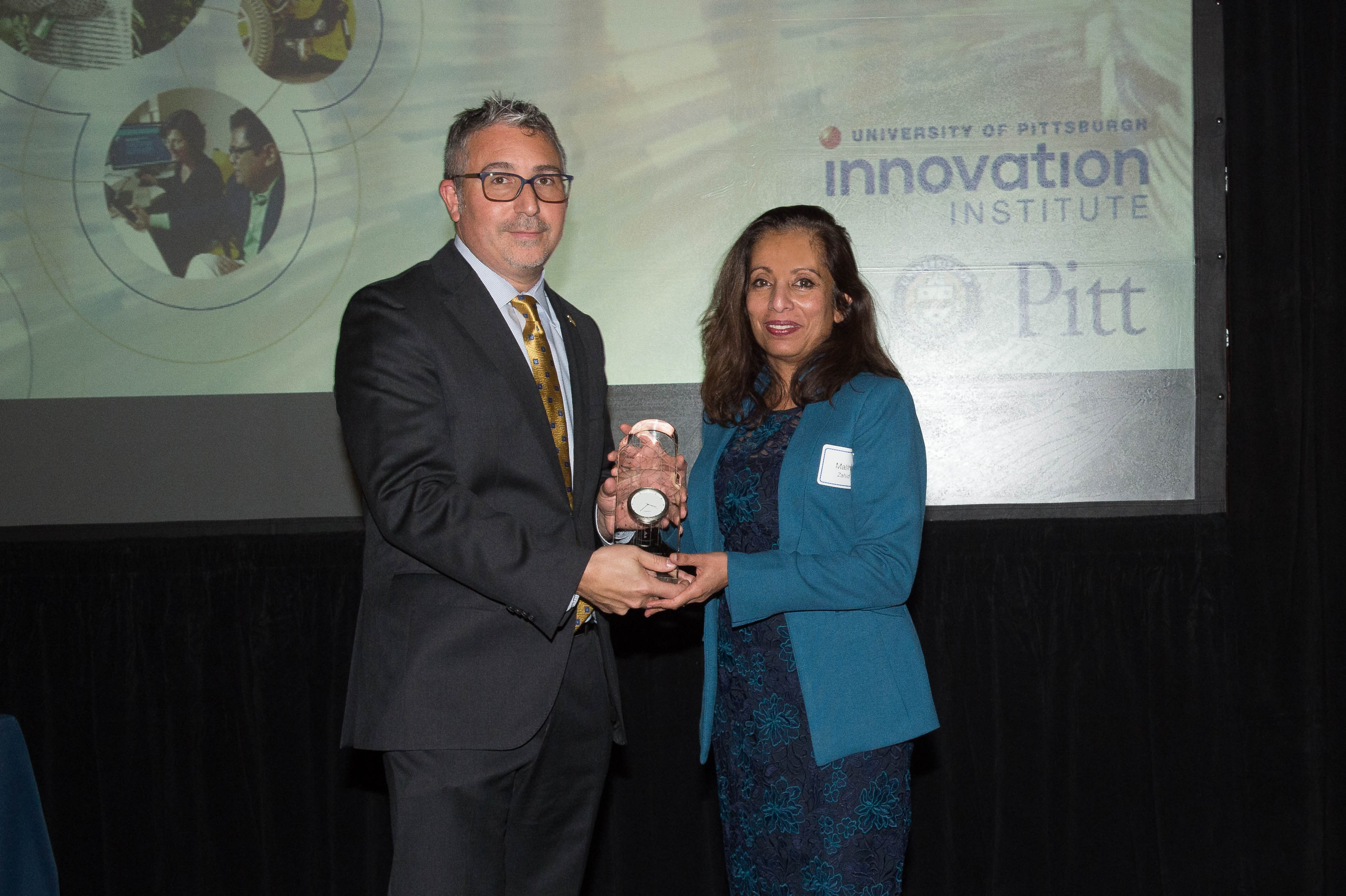 Dr. Mahila Zahid, assistant professor in the Department of Developmental Biology at the University of Pittsburgh is presented with the Emerging Innovator award by Evan Facher, Director of the Innovation Institute and Vice Chancellor for Innovation & Entrepreneurship.